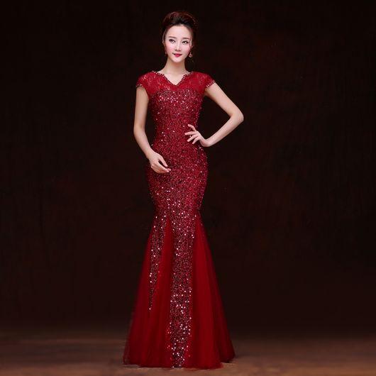 Modelo usa vestido cor vinho, com detalhes de pedrarias.