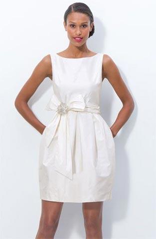 Modelo usa vestido branco, com detalhe de laço, modelo social.