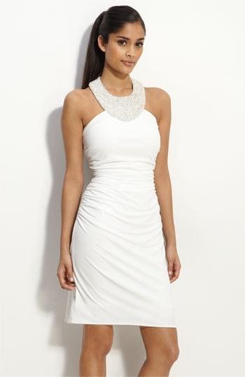 Modelo usa vestido branco, com detalhes de cinza no colo.