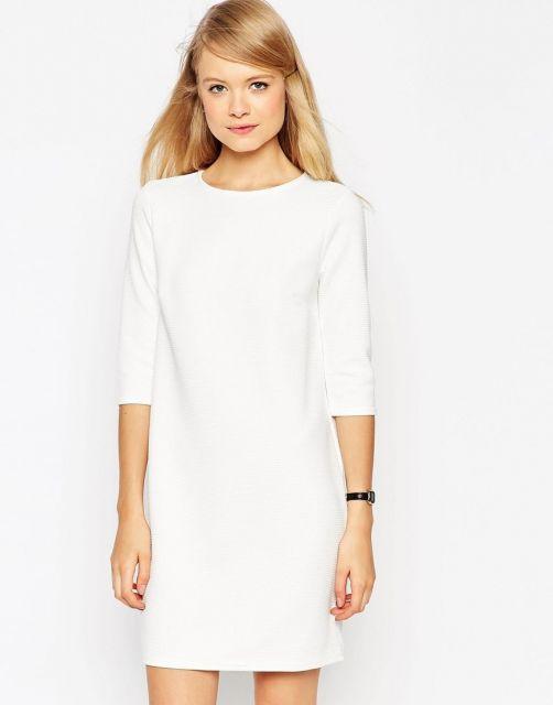 Modelo usa vestido branco social liso, sem detalhes.