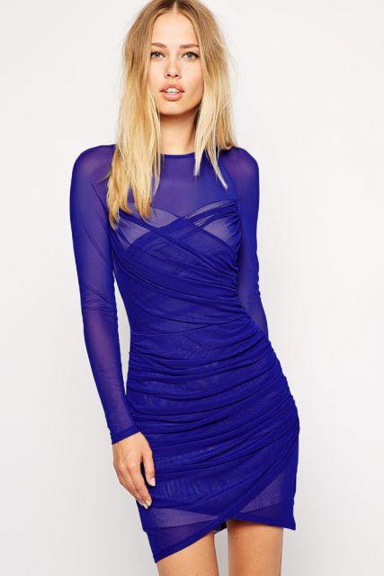 Modelo usa vestido azul bic, manga longa social com transparências.