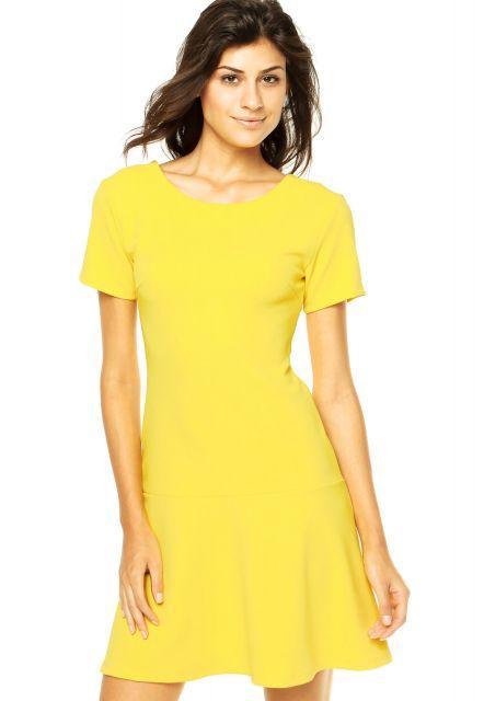 Modelo usa vestido amarelo de manguinhas, corte evasê.