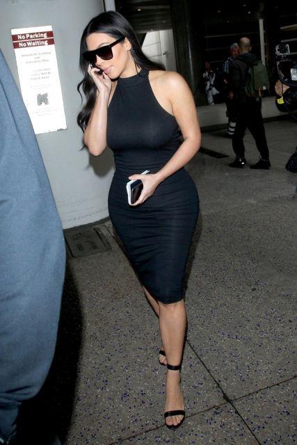 Kim kadarshian usa vestido preto social com sandalia no mesmo tom.