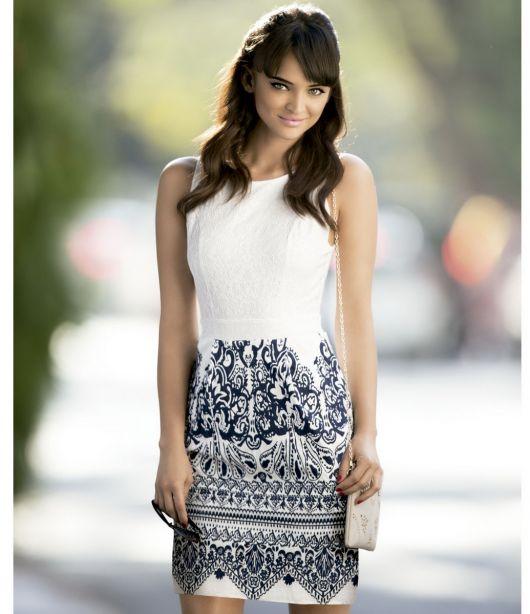 Modelo usa vestido branco com estampa preta localizada na saia da modelagem.
