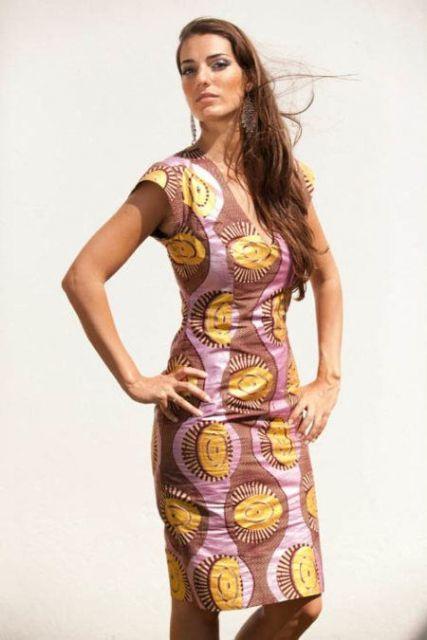 Modelo usa vestido estampado nos tons de amarelo, rosa e roxo, envelhecido.