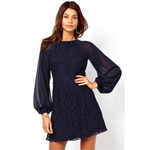 Modelo usa vestido de renda com mangas bufantes transparentes, na cor azul escuro.