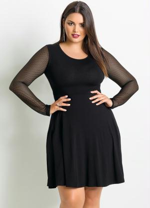 Modelo plus size usa vestido preto com detalhes de transparencias nas mangas.