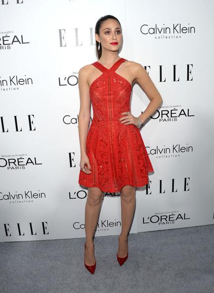 Look com vestido vermelho cavado, curo, sapato scarpin vermelho e cabelos presos em rabo de cavalo.