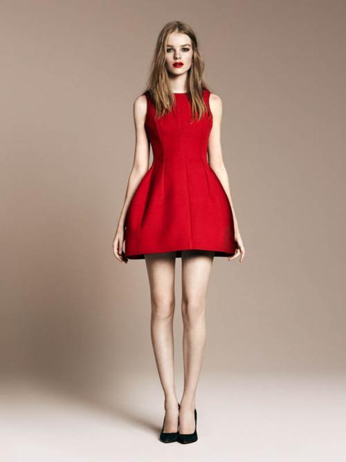 Modelo usa vestido vermelho com detalhe preto, sapato preto e cabelo solto.