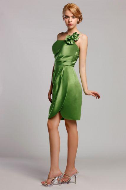 Modelo veste vestido verde claro em cetim, com cabelo preso e sandalia tiras finas.
