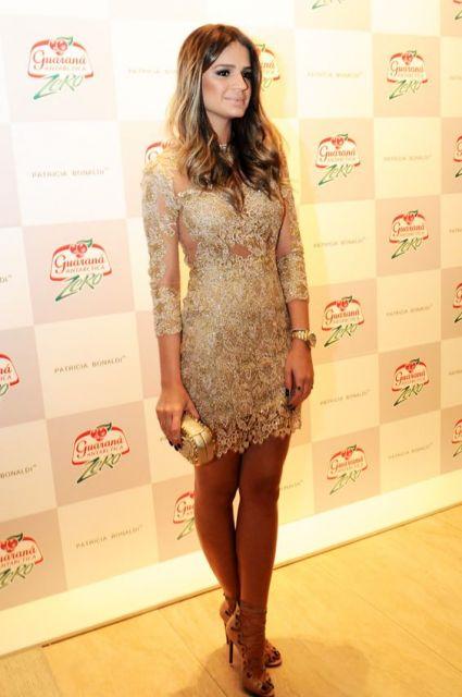 Thassia Naves veste vestido meia manga com clutch dourada, de cabelos soltos.