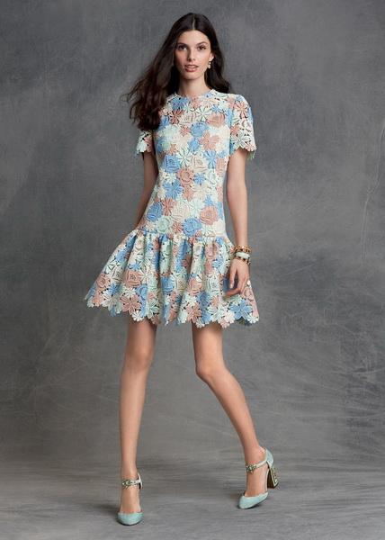 modelo usa vestido azul com detalhes rosê de estampa, curtinho com sapato de salto e cabelos soltos.