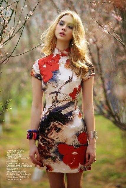 modelo veste vestido curo de manguinhas com detalhes florais grandes.