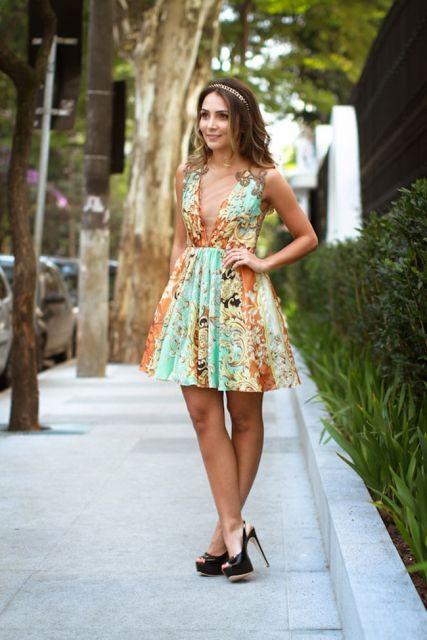 Modelo veste vestido curto com detalhes em renda, nas cores dourado e verde agua com sapato preto e cabelos soltos.