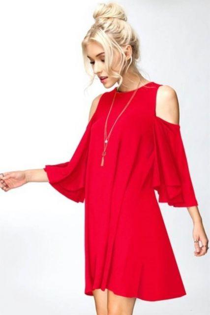 modelo usa vestido vermelho largo com corrente de prata e cabelo preso.