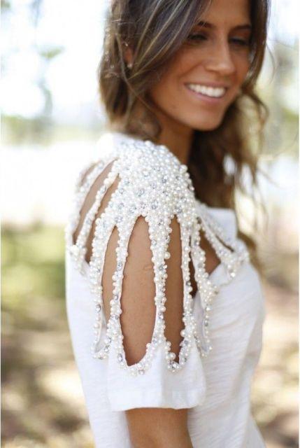 Modelo com blusa branca de detalhes vazados na manga coberta por pérolas.
