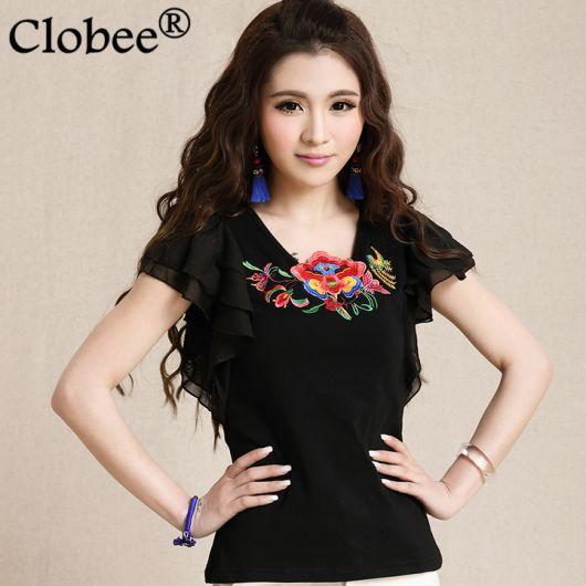 Modelo usa blusa preta bordada com detalhe no decote de mangas curtas.