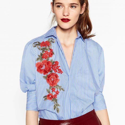 Modelo usa blusa camisa com detalhe de flores vermelhas com verde.