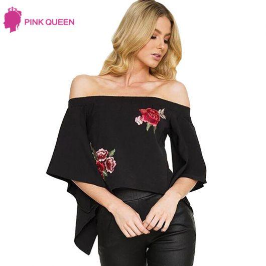 Modelo usa calça preta e blusa preta ombro a ombro com flor vermelha bordada.