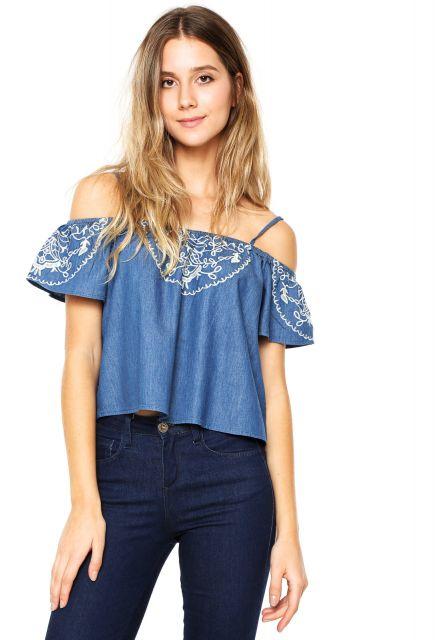 Modelo usa calça jeans escura, blusa jeans azul clara ombro a ombro com tirinhas e bordado discreto.