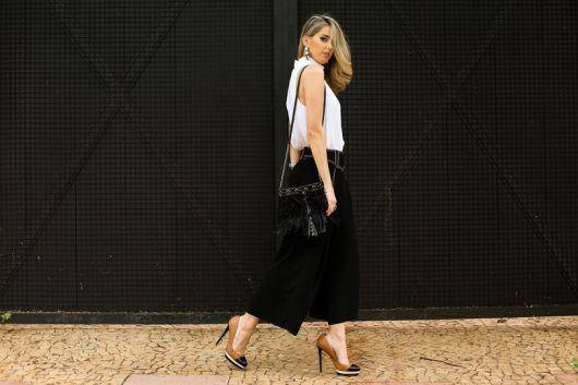 Modelo usa calça preta pantacourt, blusa regata larga branca e sapato de salto caramelo, com ponta preta e bolsa preta de franjas.