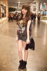 Modelo usa camiseta preta com estampa, bolsa e short na mesma cor.