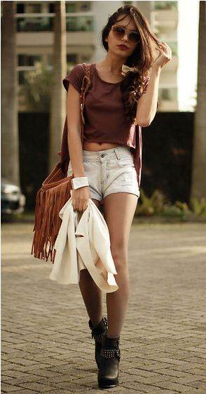 Modelo usa short jeans branco, bota caramelo, blusinha simples e bolsa caramelo.
