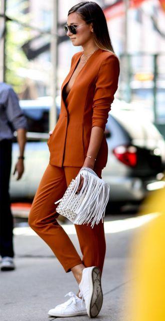 Modelo usa terninho tons terrosos e bolsa branca de franjas.