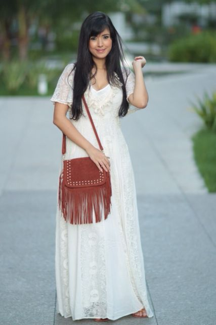 Modelo veste vestido longo branco, bolsa de franjas na cor vermelho tijolo.