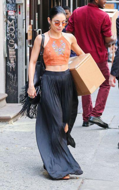Vanessa Hudgens usa blusa tons terra, saia preta de fenda e bolsa de franja.