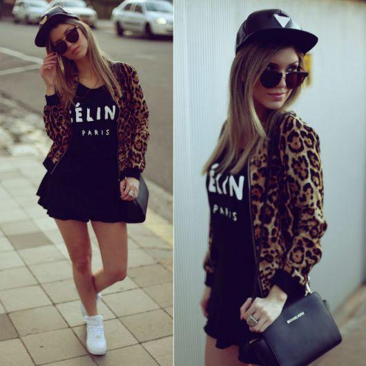 modelo usa vestido preto, bone preto, casaco animal print e tenis branco.