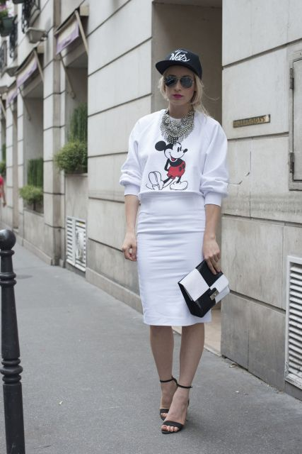 Modelo usa saia branca, moletom cropped , sandalia preta e bolsa preta e branco.