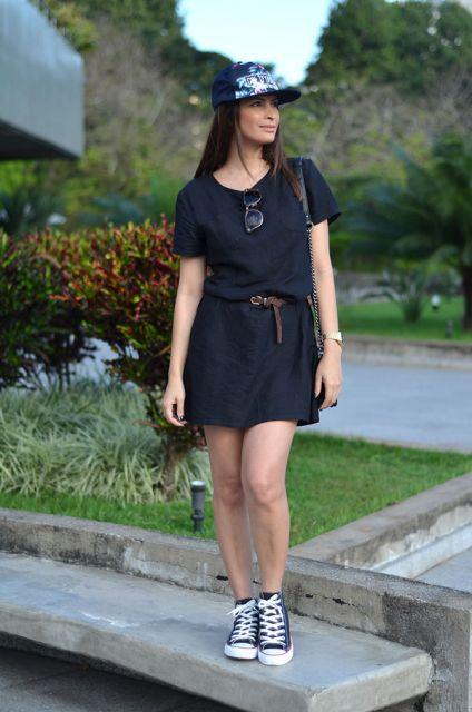 Modelo usa vestidinho preto, all star e bone aba reta azul.
