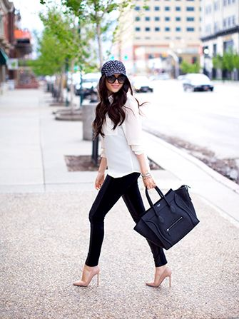 Modelo veste blusa branca, calça preta, scarpin nude, boné preto e bolsa na mesma cor.