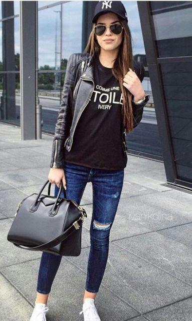Modelo usa blusa preta, jaquetinha de couro, calça jeans e tenis branco.