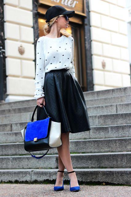 Modelo usa saia midi preta, blusa branca, boné feminino e sapatinho azul.