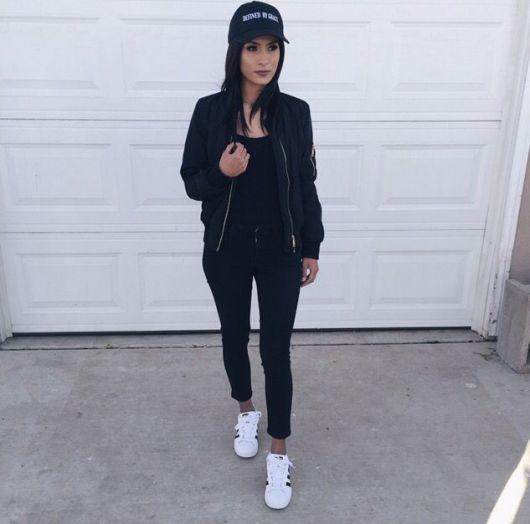 Modelo usa calça leggig, blusa, jaqueta e boné preto e tenis branco.