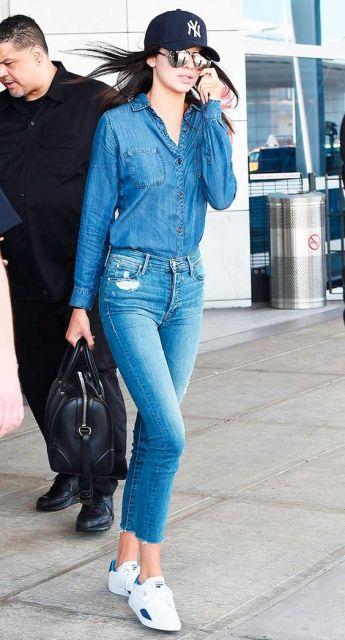 Modelo usa camisa jeans, calça jeans tenis branco e boné feminino.