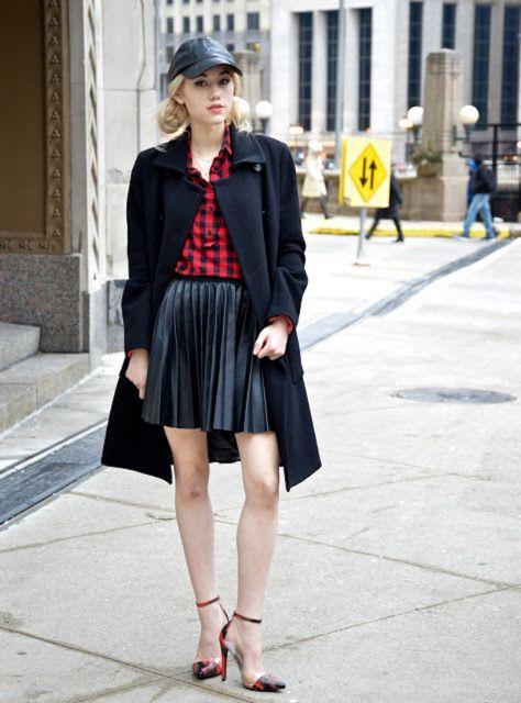 Modelo veste saia preta, casaco alongado, blusa vermelha e sapato preto.