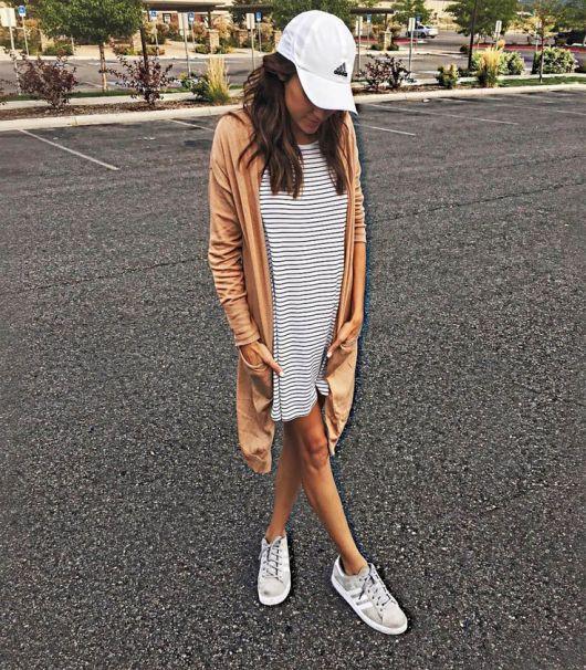 Modelo usa vestido listrado, sobreposição alongada, tenis e boné branco.