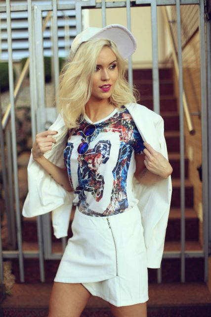 Modelo usa saia branca, blusa estampada, blazer branco e bone feminino.