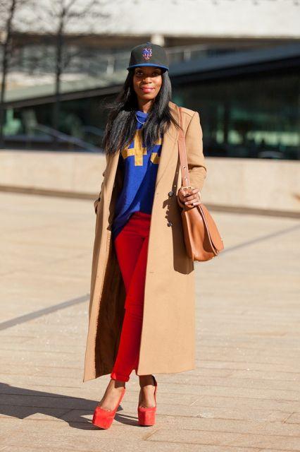 Modelo usa casaco tom terra, calça vermelha bone azul, blusa na mesma cor e sapato em tom vermelho.