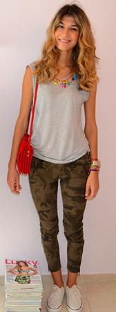 Modelo usa camiseta regata cinza, calça verde camuflada e bolsa vermelha.
