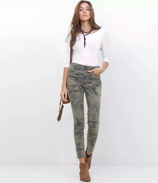 Modelo usa botinha tons terrosos, calça camuflada e blusa branca meia manga.