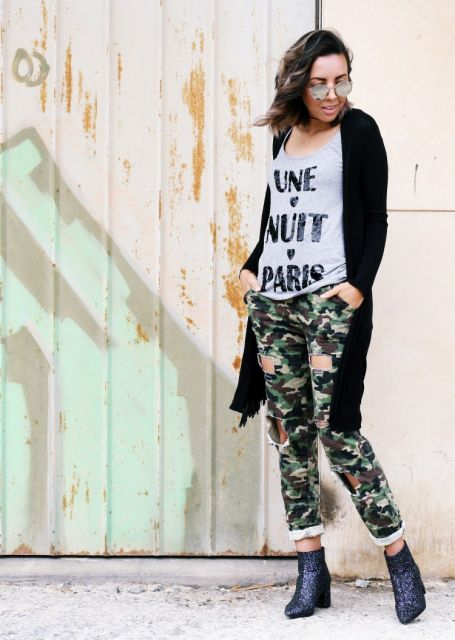 Modelo usa blusa cinza, calça verde camuflada, sobreposição preta longa e botinha cinza escuro com brilhos.