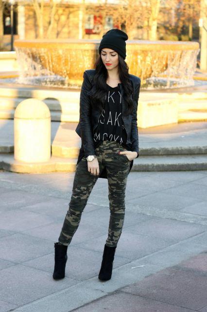 Modelo usa calça camuflada verde, botinha preta, blazer preto e botinha preta.