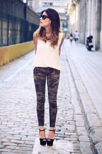 Modelo usa blusa cor rose, calça camuflada e sandalia meia pata preta.