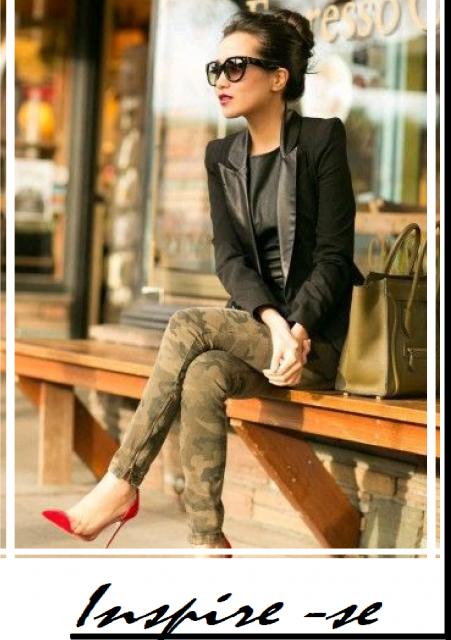 modelo sentada usa calça camuflada. blazer preto e sapato scarpin vermelho.