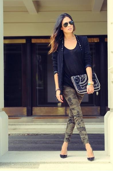Modelo usa blazer preto, calça verde camuflada, bolsa grande preta de mão e scarpin preto.