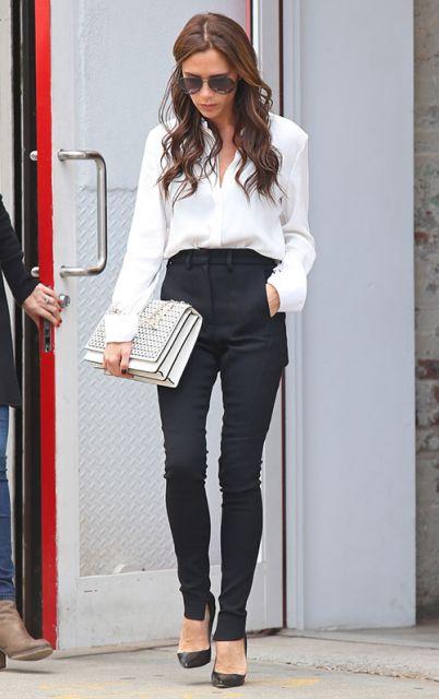 Modelo usa camisa branca manga longa, calça preta social cintura alta e scarpin preto com bolsa branca de mão.